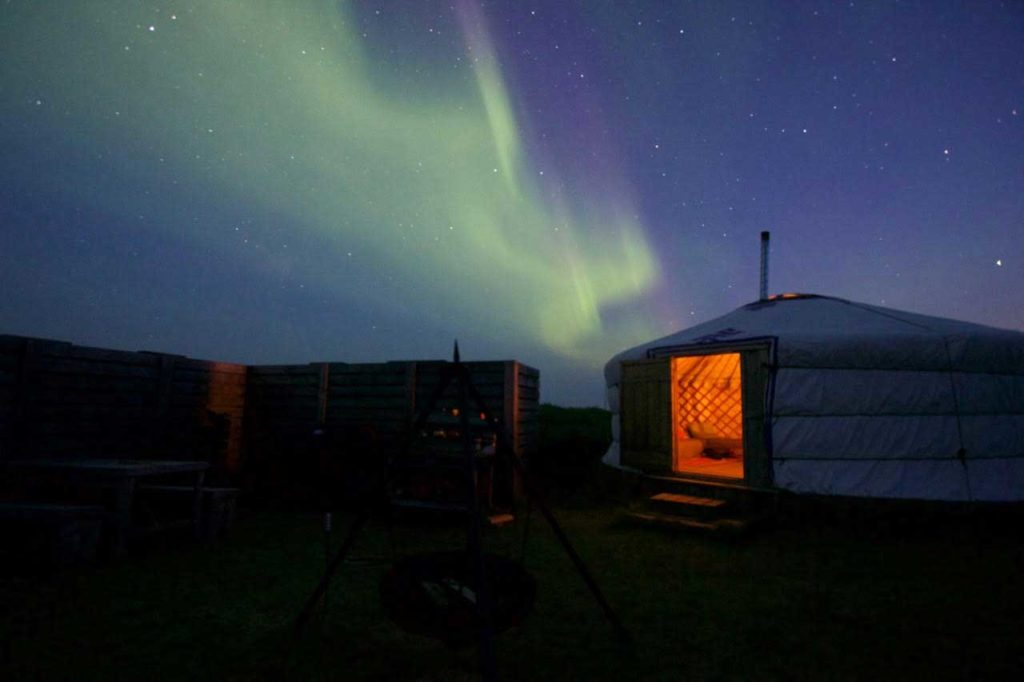 Mongolian-style yurt with the northern lights in the background.