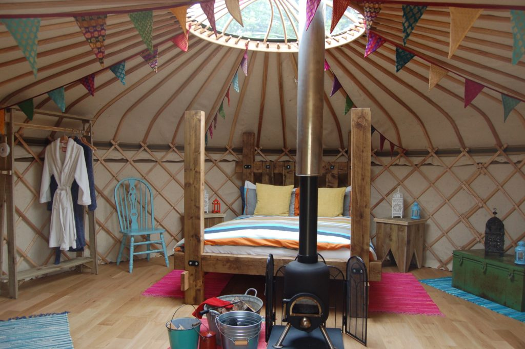 A cozy yurt with a reclaimed wood bed and a wood-burning stove.