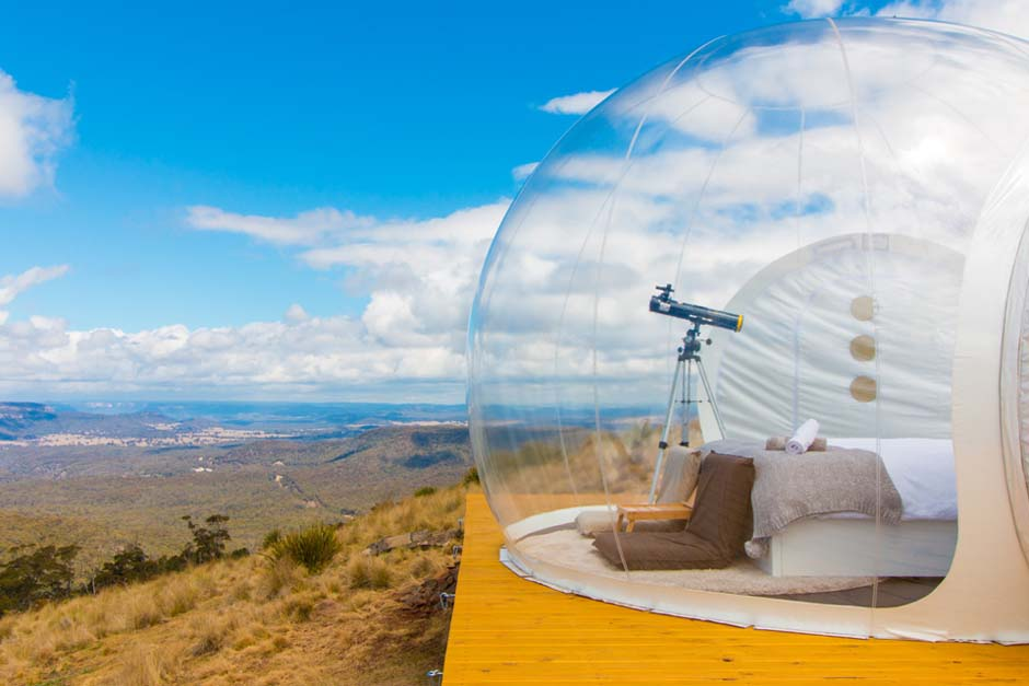 A bubble tent with a telescope, bed and chairs.