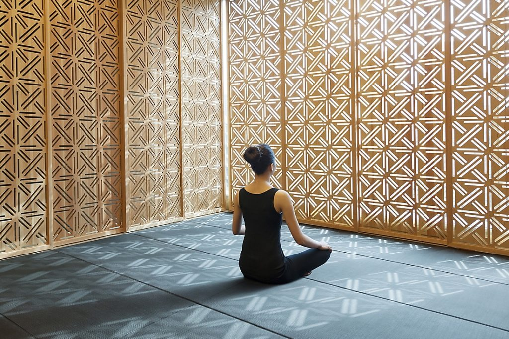 Woman meditating in a room with gold walls with light shinning through.