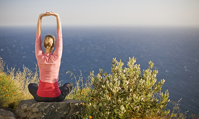 woman doing yoga on a rock overlooking the ocean